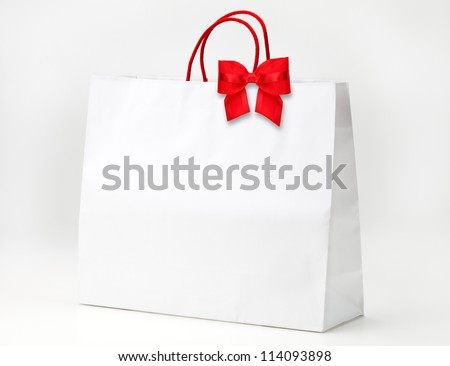 White shopping bag with red bow on white. - stock photo