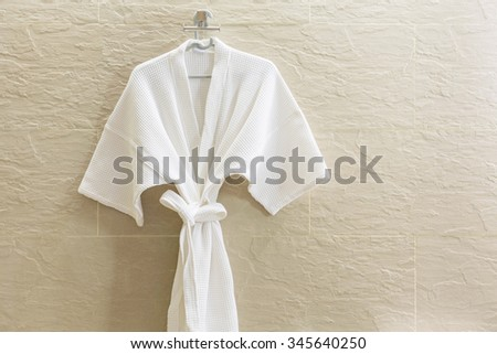 White shower gown  hanged in the bathroom with stone tiles wall background. - stock photo