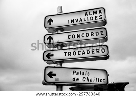 White sign directing to Paris sites and landmarks. - stock photo