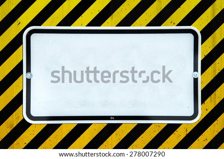 White sign on a concrete wall with yellow and black stripes