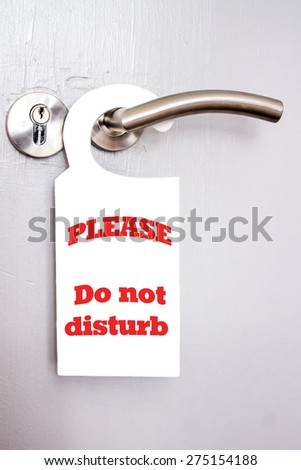 """White signal of  """"Please do not disturb"""" hanging on a door handle of hotels - stock photo"""