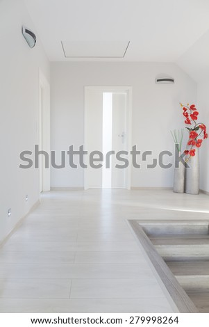 White simple corridor with floral decorations in home staircase - stock photo