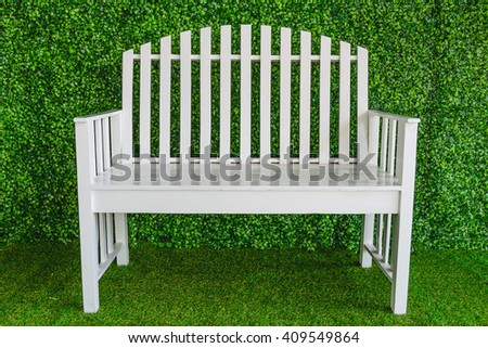 White single wooden chair on the grass in a garden - stock photo