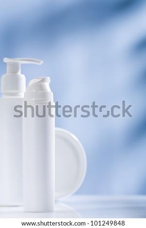 white skincare items on blue background - stock photo