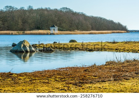 White small gazebo by the waters edge in early spring. - stock photo