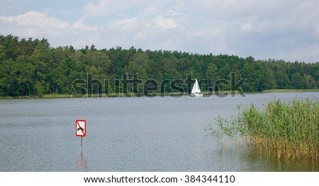 White small yachts against forest sails under cloudy sky,Mazurien Region,Poland,Europe - stock photo