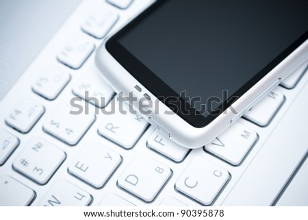 white smart phone on laptop keyboard background