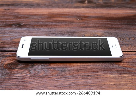 White smart phone with blank screen lying on wooden table