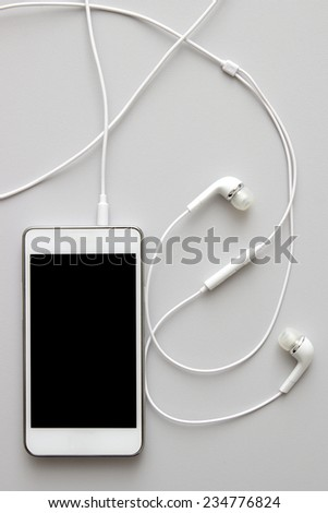 White smart phone with earphones and isolated screen on table, from above - stock photo