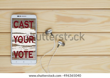 White Smartphone with an inscription, SLOGAN on the display CAST YOUR VOTE. concept of people make choices