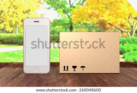 White smartphone with empty screen and package box on a table front view. Spring or summer scene. - stock photo