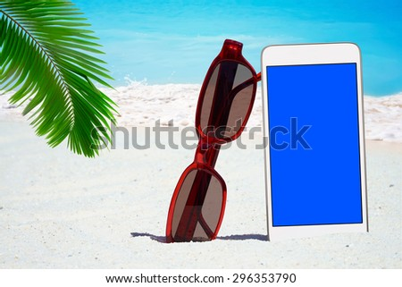 White Smartphone with empty screen display and Sunglasses on the Beach