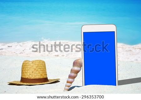 White Smartphone with empty screen display, Seashell and a Straw hat on the Beach
