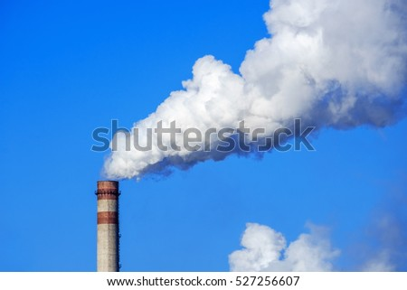 White smoke and steam from a high chimney of a power plant against a bright blue