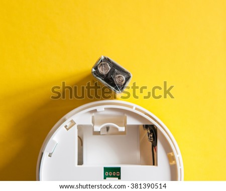 White smoke detector with nine volt battery on yellow background. A smoke detector is a device that senses smoke, typically as an indicator of fire. - stock photo