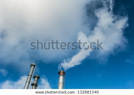 White smoke from coal powered plant stacks, profiled on bright blue sky