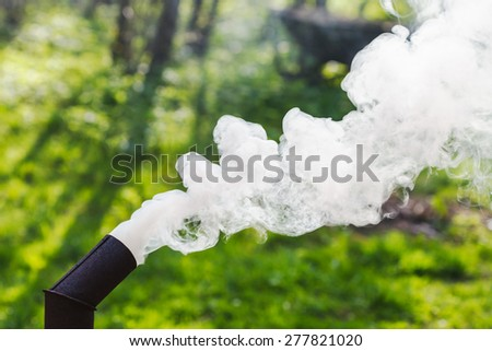White smoke from the pipe of a samovar on backyard - stock photo