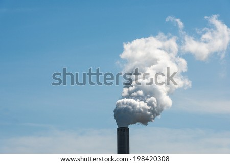 White smoking industrial chimney against a bright blue sky on a sunny day in summertime. - stock photo