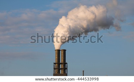 White Smoking industrial Chimney  in front of a  blue sky