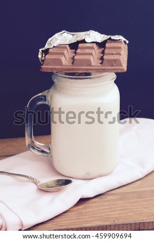 White smoothie in mason jar with chocolate bar on top on wooden table background and vintage spoon