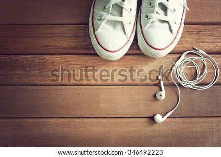 White sneakers and earphones on wooden background. Sport equipment.
