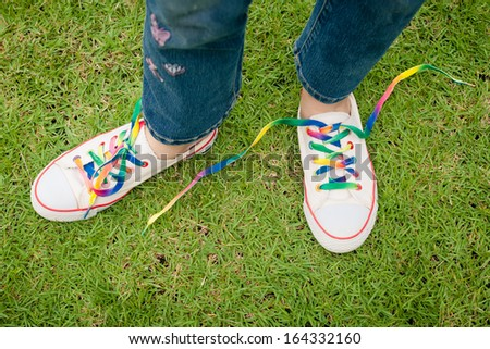 white sneakers on girl legs on grass during sunny serene summer day.