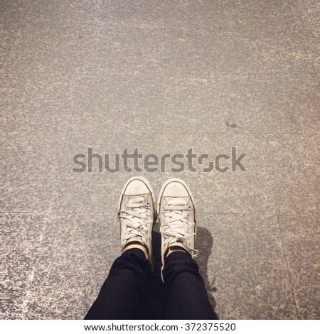 White Sneakers shoes walking on ground top view great for any use. - stock photo