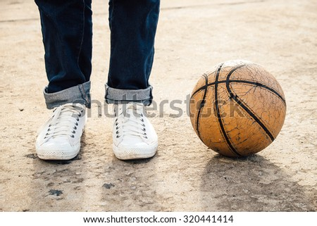 White sneakers with basketball on ground - stock photo