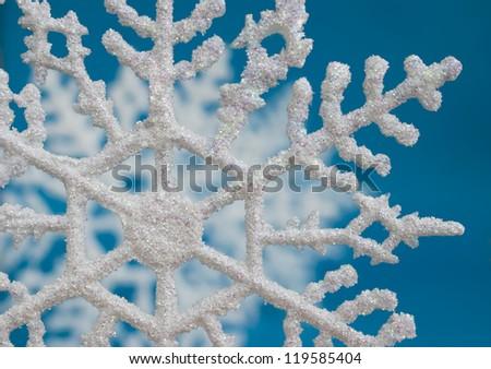 White snowflake glittering Christmas tree decoration on blue background. Winter holidays concept. - stock photo