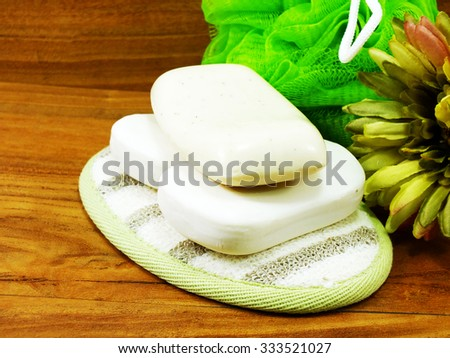 white soap and plastic bath puff on wooden background
