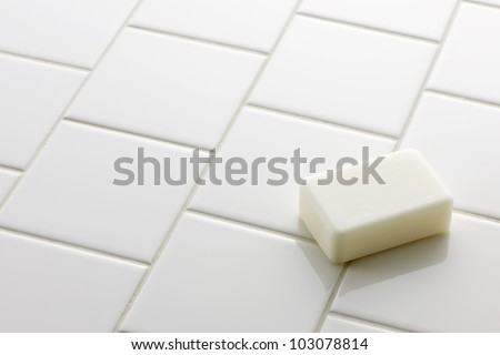 White soap bar on white tile floor - stock photo