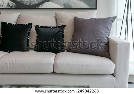 white sofa with black and grey pillows in living room interior - stock photo