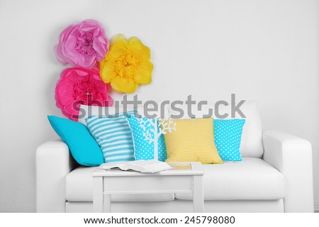 White sofa with colorful pillows in room on bright wall background - stock photo