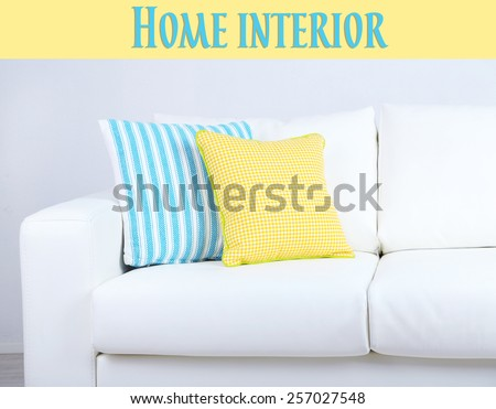 White sofa with colorful pillows on wall background, Home interior concept - stock photo