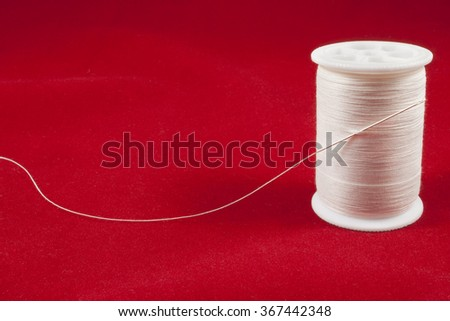 White spool of thread against a red backdrop - stock photo