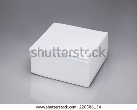 white square sheets of paper, isolated on grey background - stock photo