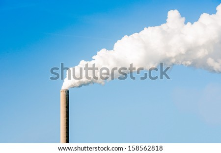 White steam and smoke emitted from a very high chimney on a bright sunny day. - stock photo