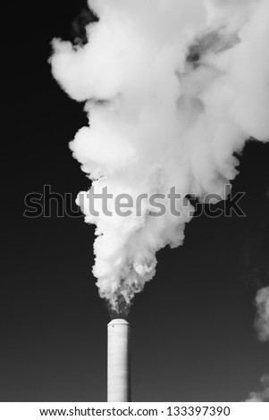 White steam rises out of a stack of a power plant