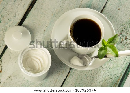 White stevia natural sweetener in powder form and a cup of coffee - stock photo