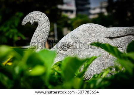 White Stone Elephant Statues behind the green leaf.