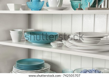 White Storage Stand With Dishware In Kitchen