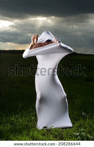 White strange ghost standing in the middle of the field against the background of gathering clouds