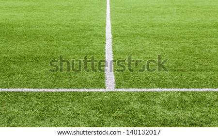 White stripe on the green soccer field from front view