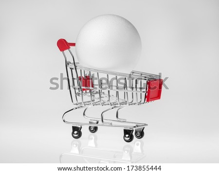 White styrofoam ball in small shopping cart placed on a white reflective background. - stock photo