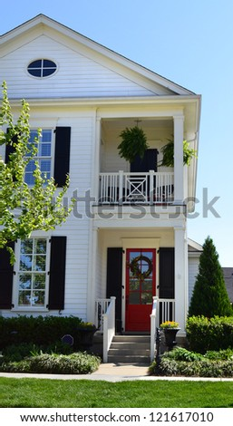 White Suburban American Cape Cod Home with Upstairs Balcony - stock photo