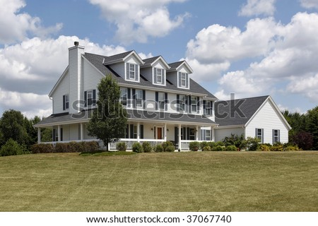 White suburban home with blue shutters and wraparound porch