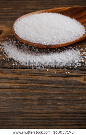 White sugar crystals spilling from wooden spoon