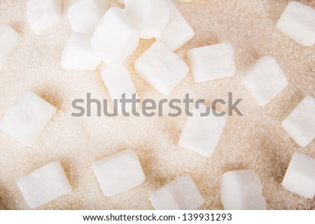 White sugar cubes and crystal sugar, on a wooden background