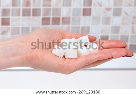 White sugar cubes pile in female hand - stock photo