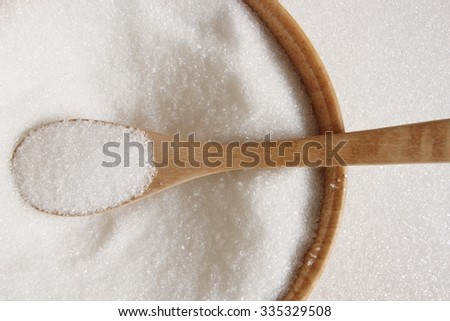 white sugar in wood spoon